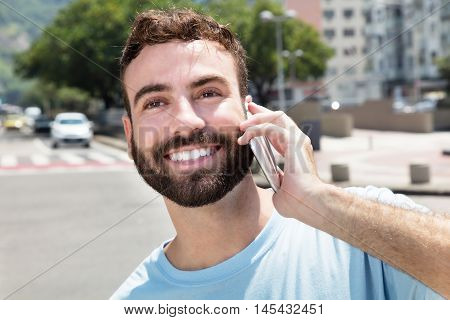 Sporty caucasian man with beard on phone outdoor in city