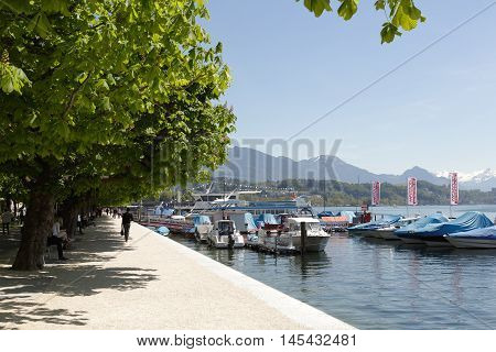 LUCERNE SWITZERLAND - MAY 06 2016: Promenade along the shore of Lake Lucerne is a walking place frequently visited by many tourists because of the magnificent views that can be seen from here