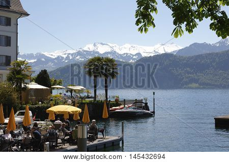 Weggis Switzerland - May 05 2016: Unknown people spend a nice time in the restaurant on the shores of Lake Lucerne in Weggis and they enjoys the beautiful views around. Weggis it is the small holiday resort placed on the shore of Lake Lucerne.