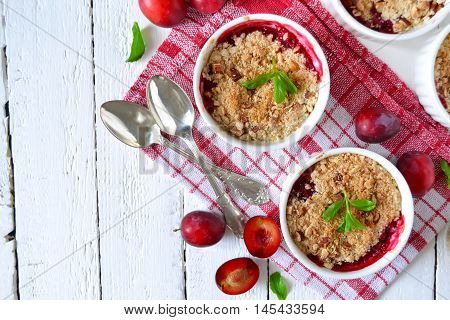 Oat crumble with plums spices and honey on a light background
