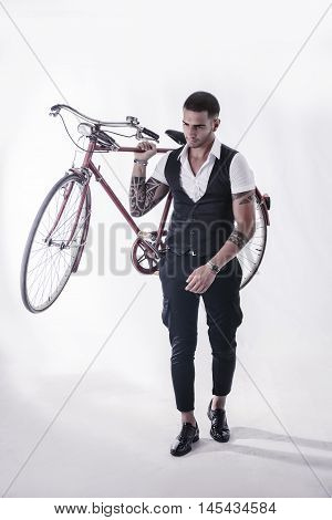 Portrait of young tattooed man in elegant clothes holding a bicycle. Studio shot. Full body shot