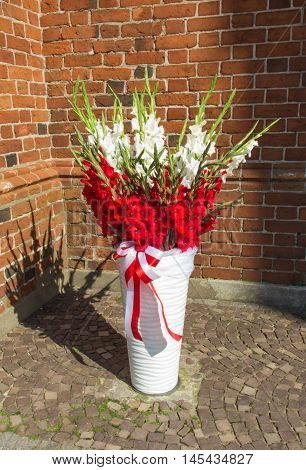 white and red flowers in a vase with a sash in the colors of the national Polish