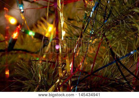 The shining fires of a fir-tree garland on a fir-tree branch