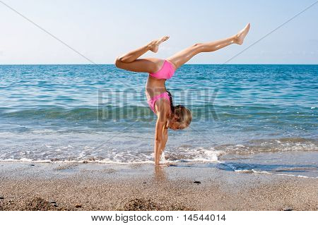 Schoolgirl Making Gymnastics On Seashore