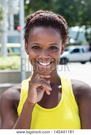 Portrait of an african american girl with yellow shirt and short hair outdoor in the city in the summer