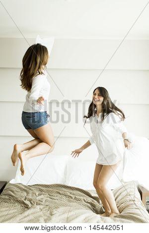 Women Having Fun On Bed