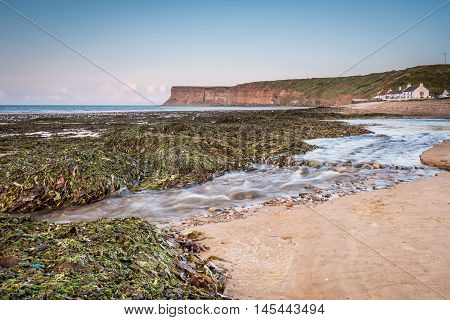 Skelton Beck and Saltburn Scar, which flows over Saltburn Sands into the North Sea with Saltburn Scar behind