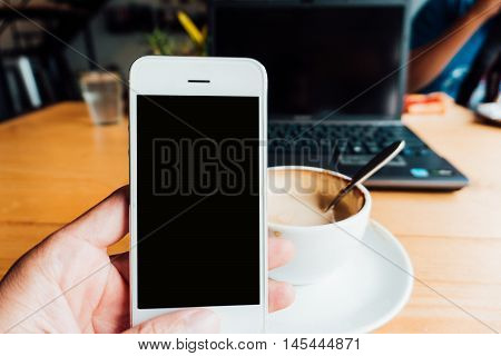 Man Using Blank Smartphone With Coffee And Dessert