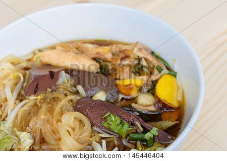 noodle soup in bowl on a wooden table Thai local food