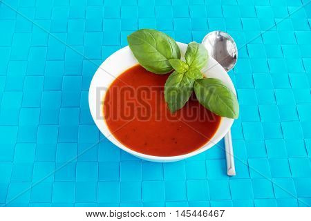 Tomato and basil soup in a white soup bowl decorated with basil leaves and served on a blue place mat and soup spoon.