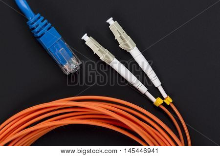 Blue twisted pair patch cord with fiber optics orange cable on dark background.
