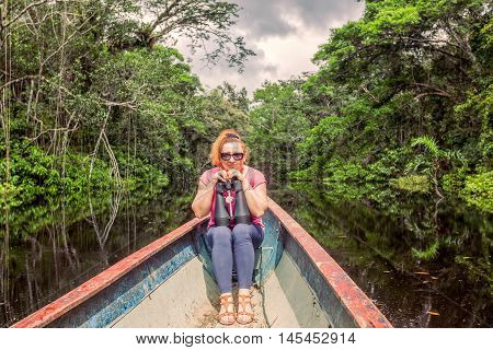 Happy Tourist Woman In A Canoe With High Power Binocular In Amazonian Jungle National Park Cuyabeno South America