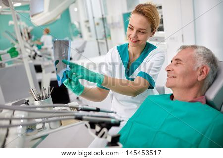 Female dentist showing teeth problem on dental X-ray to patient