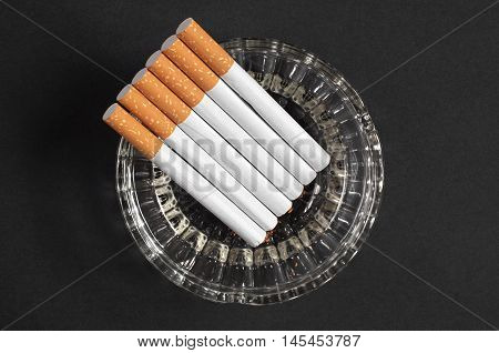 Glass ashtray with cigarettes on black background top view