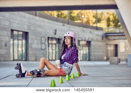 Happy young girl enjoying roller skating with coffee, rollerblading on retro skates sport in urban park. Woman in outdoor activities. Active lifestyle.