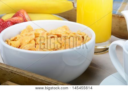 Close up of breakfast tray with orange juice cereals and fruits.