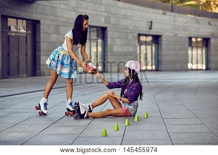 Girl fall down and scratch the leg after rollerblading. Beautiful young woman offers to help protective equipment for the knees. Two girls sports fun. Active lifestyle.