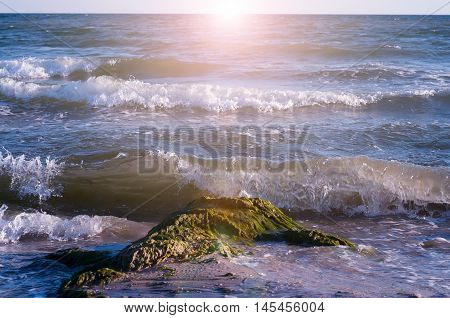 Big wave splashing. Sea water beating against the rocks and cliffs. Blue sky above the beach in the sun zenith refreshing drops of ocean water.