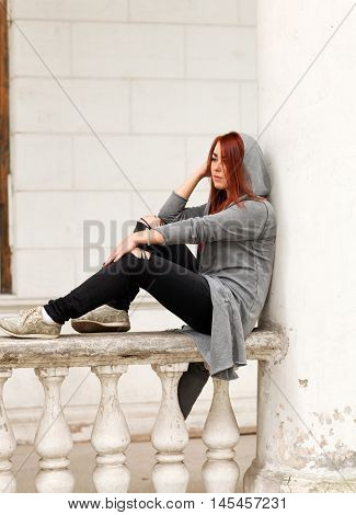 Beautiful young red-haired woman sitting on the railing of the old