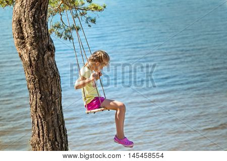 little girl swinging on seesaw above a sea