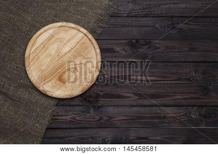 Empty vintage cutting board on dark wooden planks food background concept