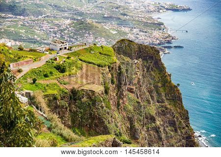 High angle view of grassy and rocky cliff overlooking vast blue ocean from Madeira Portugal