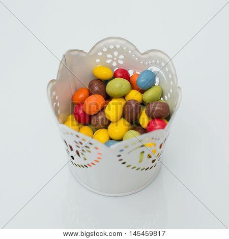 Colorful candy in a pot on a white background