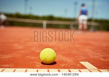 Close up of yellow tennis ball on red clay
