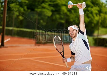 Happy male tennis player with goblet and racket after match