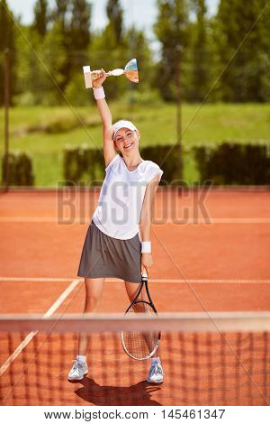 Young female tennis winner with goblet on tennis court