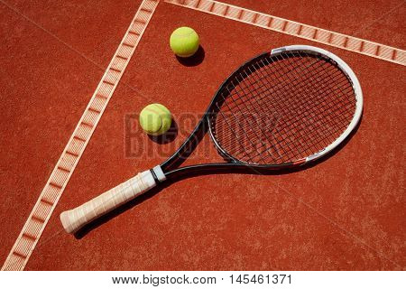 Close up of racket and balls on tennis terrain at red dross