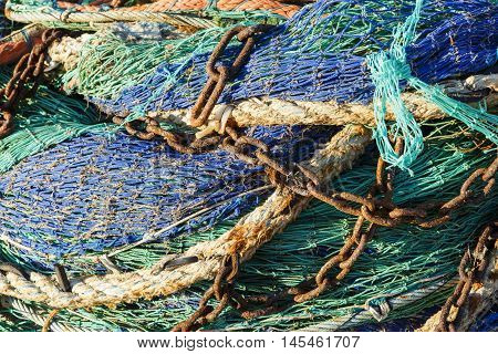 Fishing net with rusty chains Close-up of green and blue fishing net with rusty chains and old ropes
