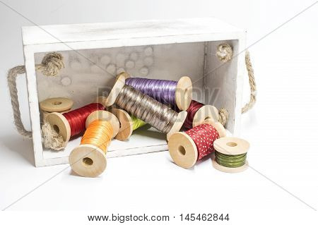 Spools with ribbons in several Colors and a wooden box