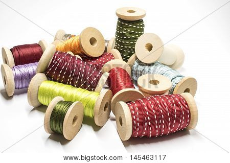 A heap of several ribbons on wooden spools