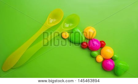 plastic spoon for baby feeding on green table