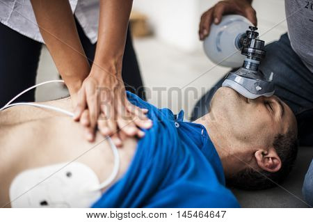 operators assisting an unconscious man with cardiopulmonary resuscitation and heart massage