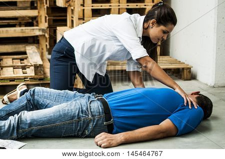 girl helping an unconscious guy after heart attack