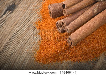 cinnamon sticks with powder on the wood table