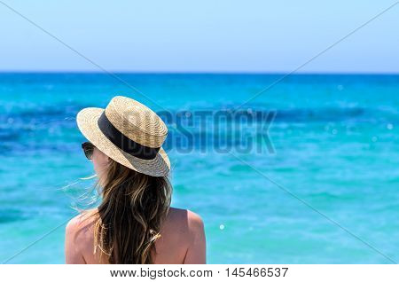 Portrait of young adorable caucasian woman in sunglasses and summer straw hat staying over background of turquoise sea at tropical exotic sandy beach in Sardegna island Italy