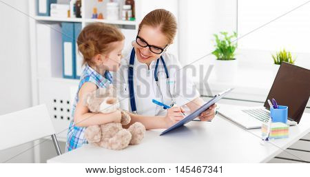 friendly happy doctor pediatrician with patient child girl in office at clinic