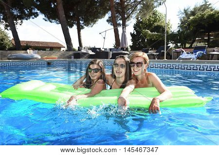 group of three happy and beautiful young girl friends having bath floating in airbed in swimming pool together having fun enjoying summer at vacation resort smiling in women holiday concept