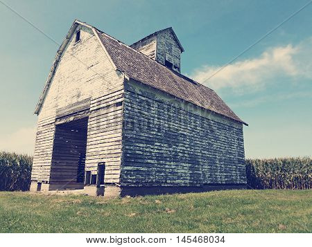 Vintage looking shot of an old barn with chipping paint in a corn field