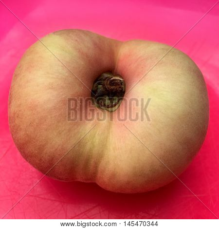 Fresh doughnut peach fruit in extreme closeup