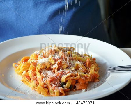 Tagliatelle with tomato sauce and parmesan on a white bowl