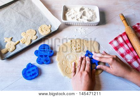 Making cookies for Halloween and Thanksgiving. Fun food for kids, a snack for a party. Woman cut out cookies using cookie cutters, hands in the frame