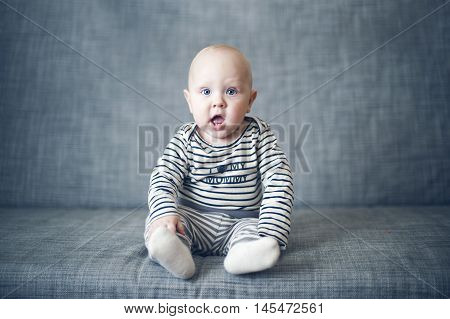 Surprised baby with open mouth sitting on gray couch