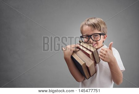 Happy smiling boy with books going back to school putting his thumb up