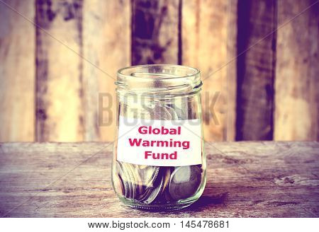 Coins in glass money jar with Global Warming fund label financial concept. Vintage tone style