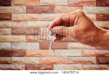 Human hand holding house key with blurred old brick wall background for any design