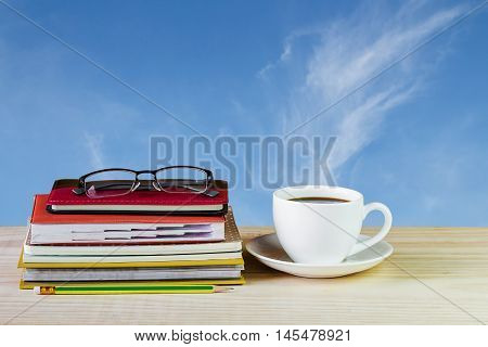 Coffee cup glasses and stack of book on wooden table with blur sky background. Business concept